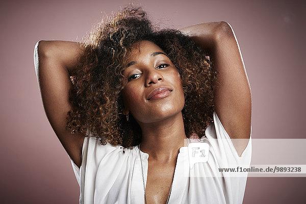 Porträt einer jungen Frau mit Händen hinter dem Kopf