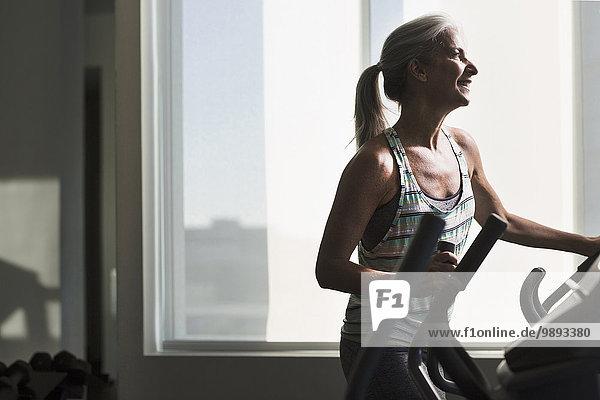 Reife Frau beim Training auf dem Fitnessgerät