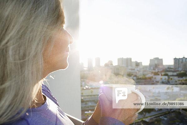 Nahaufnahme einer reifen Frau beim Kaffeetrinken auf dem Balkon der Stadtwohnung