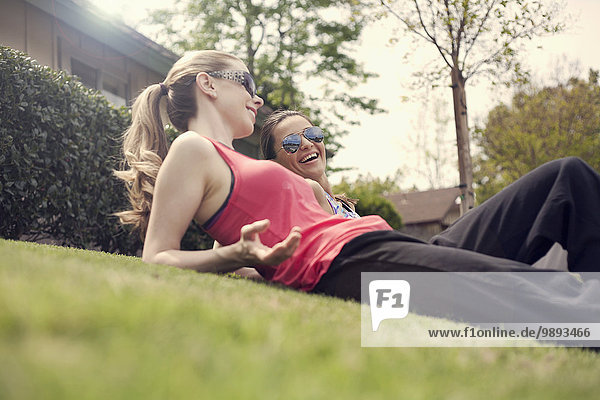 Two women relaxing on grass  chatting  low angle view