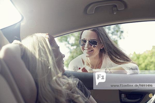 Junge Frau  die durch das Autofenster zu ihrem Freund geht.