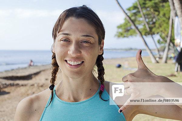 Frau macht Handbewegung am Strand