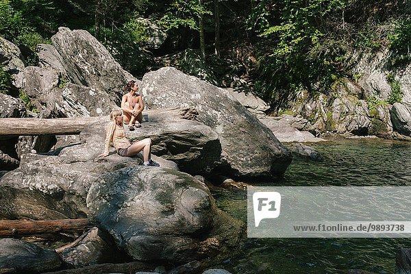 Zwei Frauen sitzen an einem Schwimmloch im Wald.
