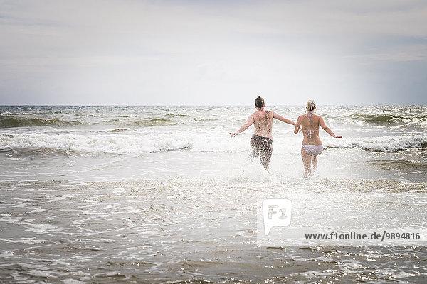 Mexiko  Riviera Nayarit  junges Paar  das ins Meer läuft