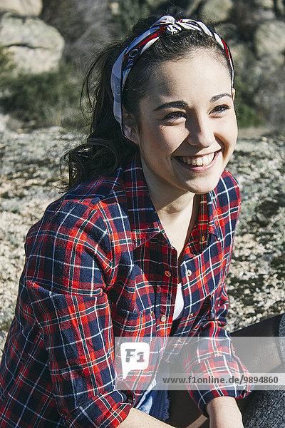Porträt einer lächelnden Frau auf einem Felsen sitzend