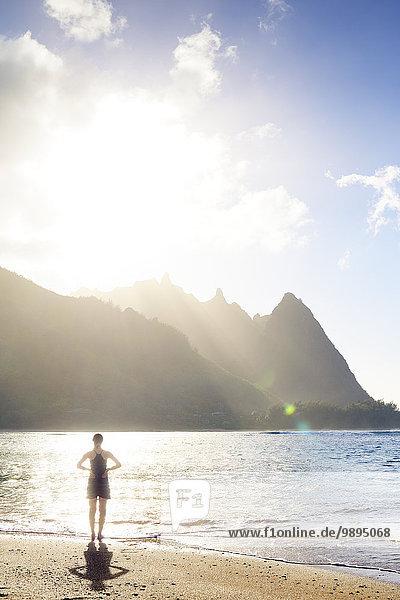 USA  Hawaii  Hanalei  Frau am Haena Beach  Blick zur Na Pali Küste im Abendlicht