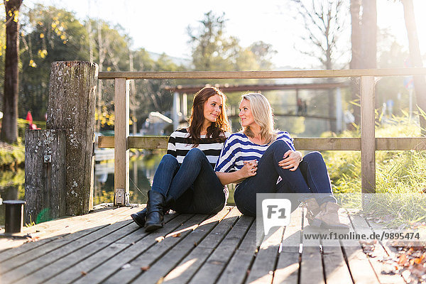 Lesbian couple in love sitting on a jetty
