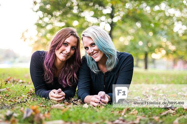 Porträt von zwei Freundinnen mit buntem Haar auf einer Wiese