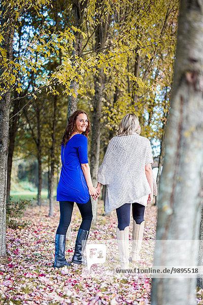 Happy lesbian couple walking in nature
