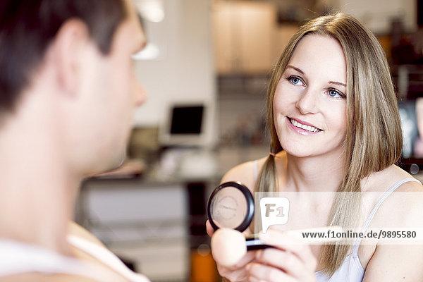 Porträt einer lächelnden Frau mit Kosmetikpinsel