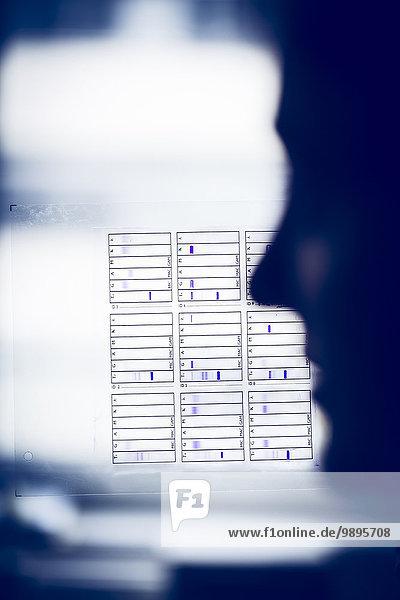 Silhouette des Laboranten mit Testblatt