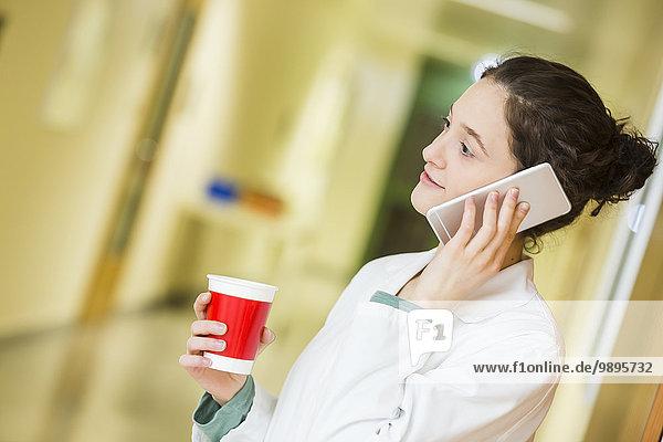 Junger Arzt mit Handy und Kaffeetasse auf dem Krankenhausboden