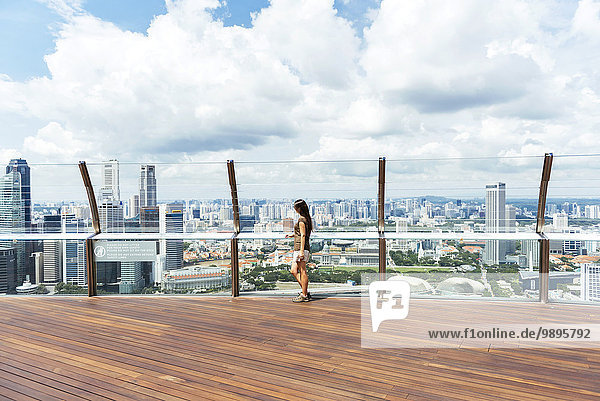 Singapore  woman standing on observation deck of Sands SkyPark looking at view