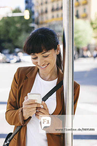 Spain  Barcelona  businesswoman with smartphone waiting at the bus stop
