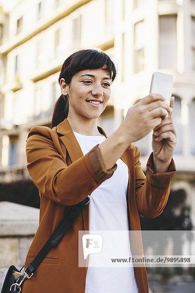 Spanien  Barcelona  lächelnde Geschäftsfrau nimmt Selfie mit Smartphone