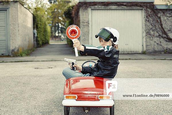 Junge im Tretauto verkleidet als Polizist