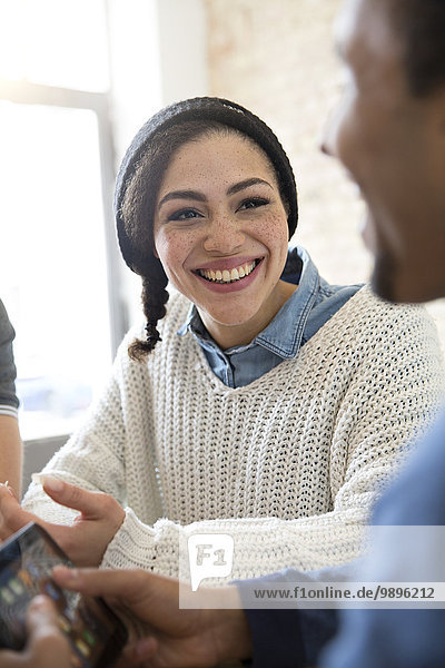 Smiling young woman looking at friend with smartphone