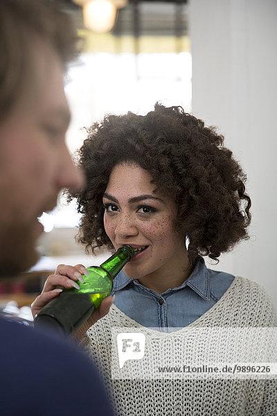 Junge Frau trinkt Bier und schaut den Mann an.