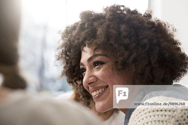 Lächelnde junge Frau trifft sich mit Freunden