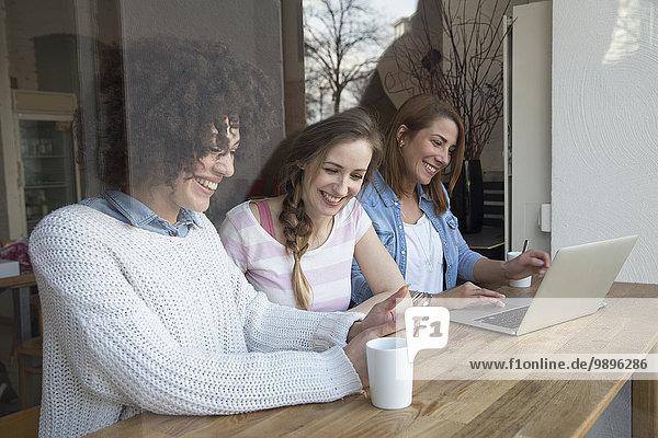 Glückliche Freundinnen mit Laptop und Handy im Café