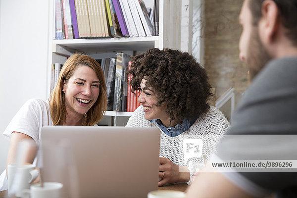 Zwei Freundinnen mit Laptop in einer Cafeteria