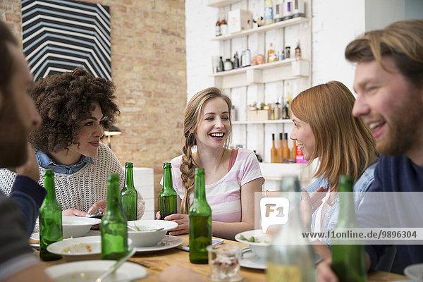 Glückliche Freunde am Esstisch mit Bierflaschen