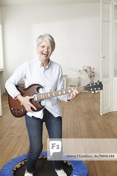 Reife Frau  die auf dem Trampolin steht und E-Gitarre spielt.