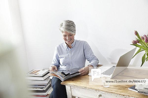 Reife Frau am Tisch sitzend mit Magazin und Laptop