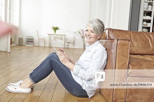 Reife Frau auf dem Boden sitzend mit digitalem Tablett