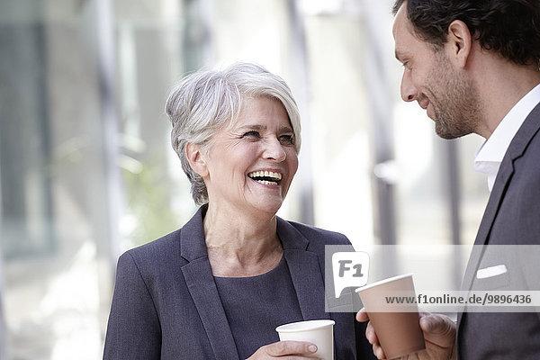 Zwei lächelnde Geschäftsleute mit Kaffee zum Mitnehmen