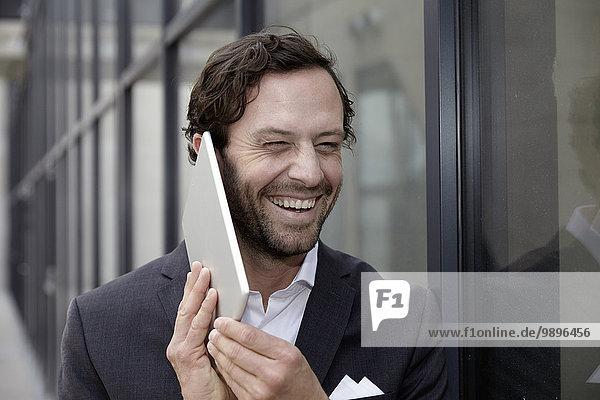 Porträt eines lachenden Geschäftsmannes  der versucht  mit seinem digitalen Tablett zu telefonieren.