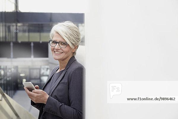Porträt einer lächelnden Geschäftsfrau mit Smartphone