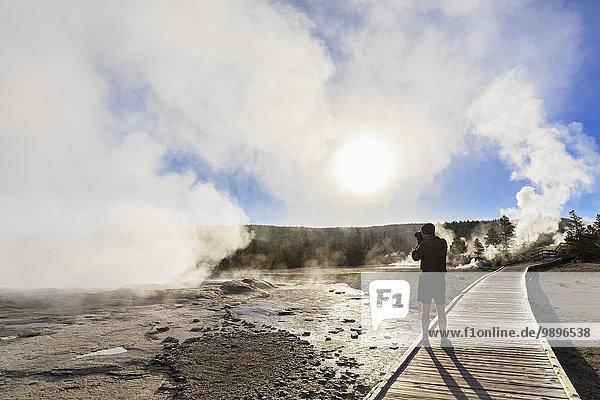 USA  Wyoming  Yellowstone Nationalpark  Lower Geyser Becken  Touristen fotografieren Dampf der Geysire am Morgen