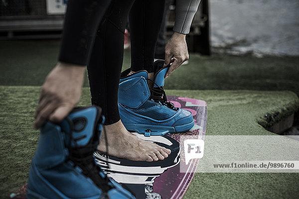 Deutschland  Garbsen  Wakeboarder beim Ausziehen der Schuhe