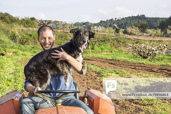 Landwirt mit Traktor auf Feldhaltehund