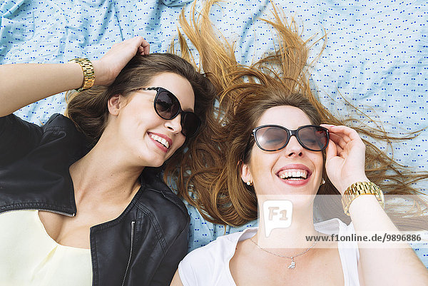 Two laughing women with sunglasses lying on blue sarong