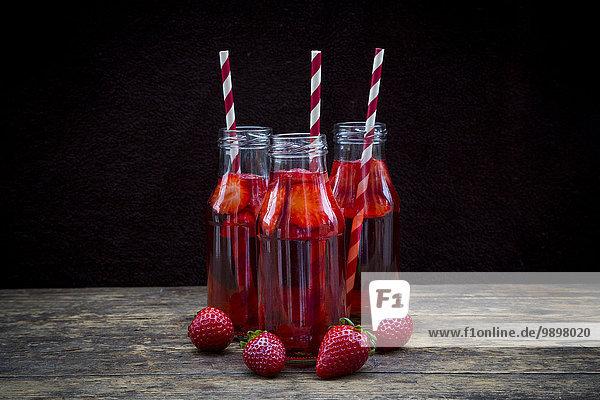 Drei Glasflaschen hausgemachte Erdbeerlimonade