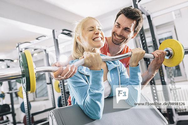 Training für junge Paare mit EZ Curl Bar im Fitnessstudio