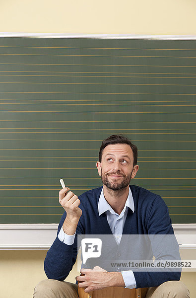 Lächelnder Lehrer im Klassenzimmer an der Tafel schaut nach oben Lächelnder Lehrer im Klassenzimmer an der Tafel schaut nach oben