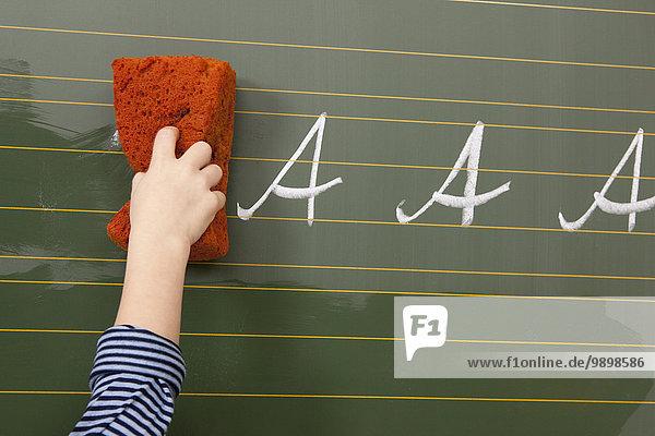 Schuljunge an der Tafel wischt den Buchstaben A ab Schuljunge an der Tafel wischt den Buchstaben A ab