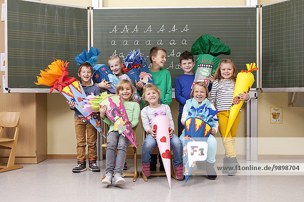 Group of happy pupils with school cones in classroom