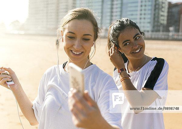 Spanien  Gijon  zwei sportliche junge Frauen mit Ohrstöpseln am Strand