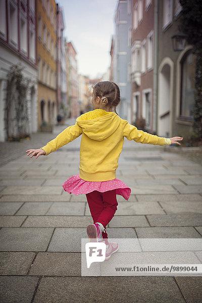 Deutschland  Bayern  kleines Mädchen tanzt in einer Gasse