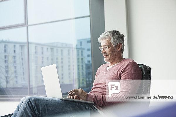Mann sitzt in einem Ledersessel mit Laptop