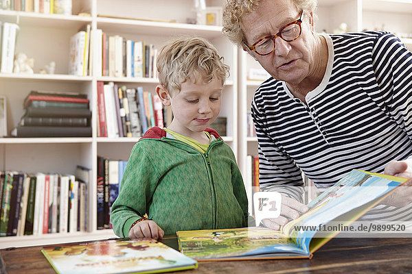 Grandfather and grandson reading children's book together
