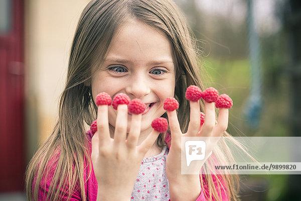 Glückliches Mädchen mit Himbeeren an den Fingern