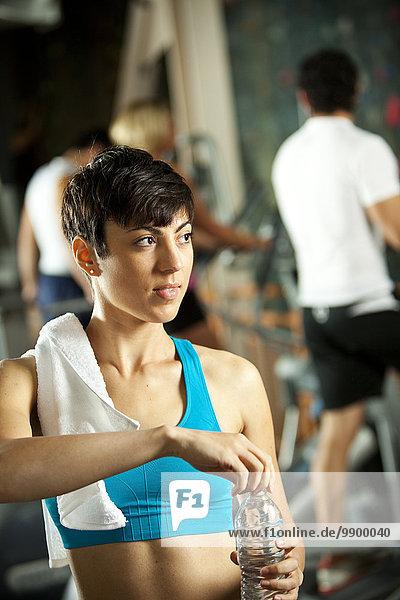 Frau mit Wasserflasche im Fitnessstudio