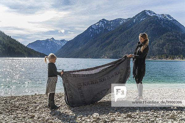 Österreich  Tirol  Plansee  Mutter und Tochter am Seeufer Faltbadetuch
