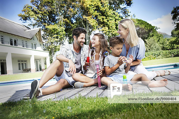 Glückliche Familie am Pool beim Spielen mit Seifenblasen