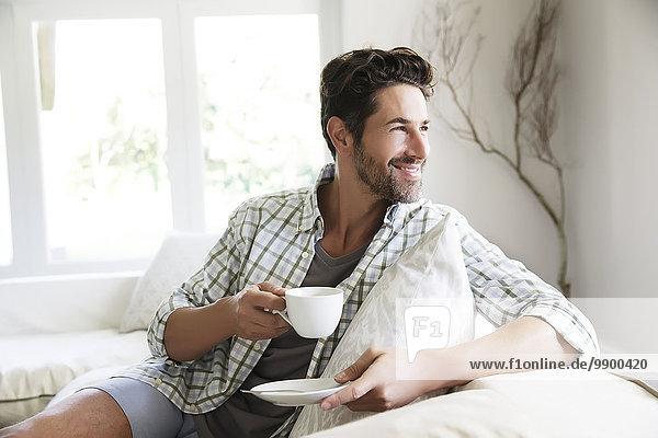 Erwachsener Mann sitzt auf dem Sofa und trinkt Kaffee.
